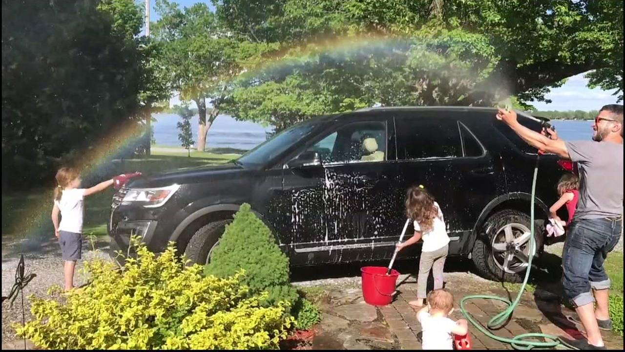 This undated photo shows David Freiheit creating a rainbow while washing a car with his children in Montreal.