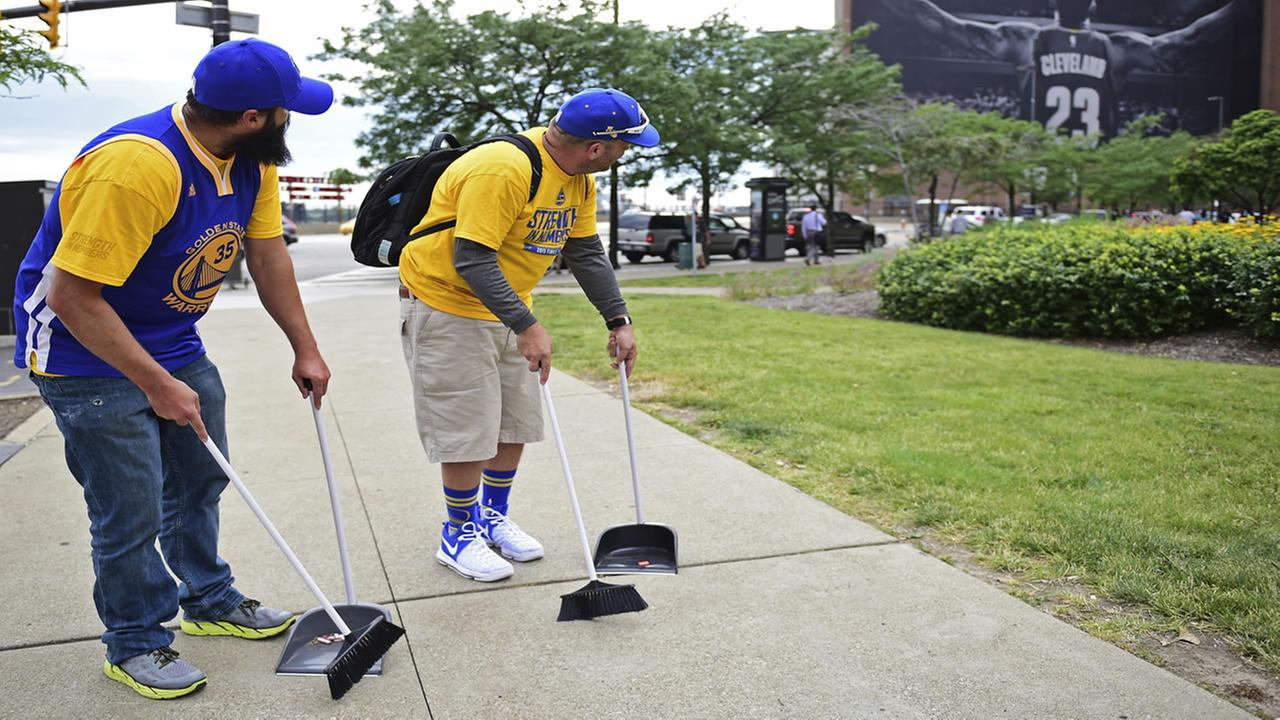 Two Warriors fans stand in downtown Cleveland near the LeBron James tribute on June 9, 2017.AP