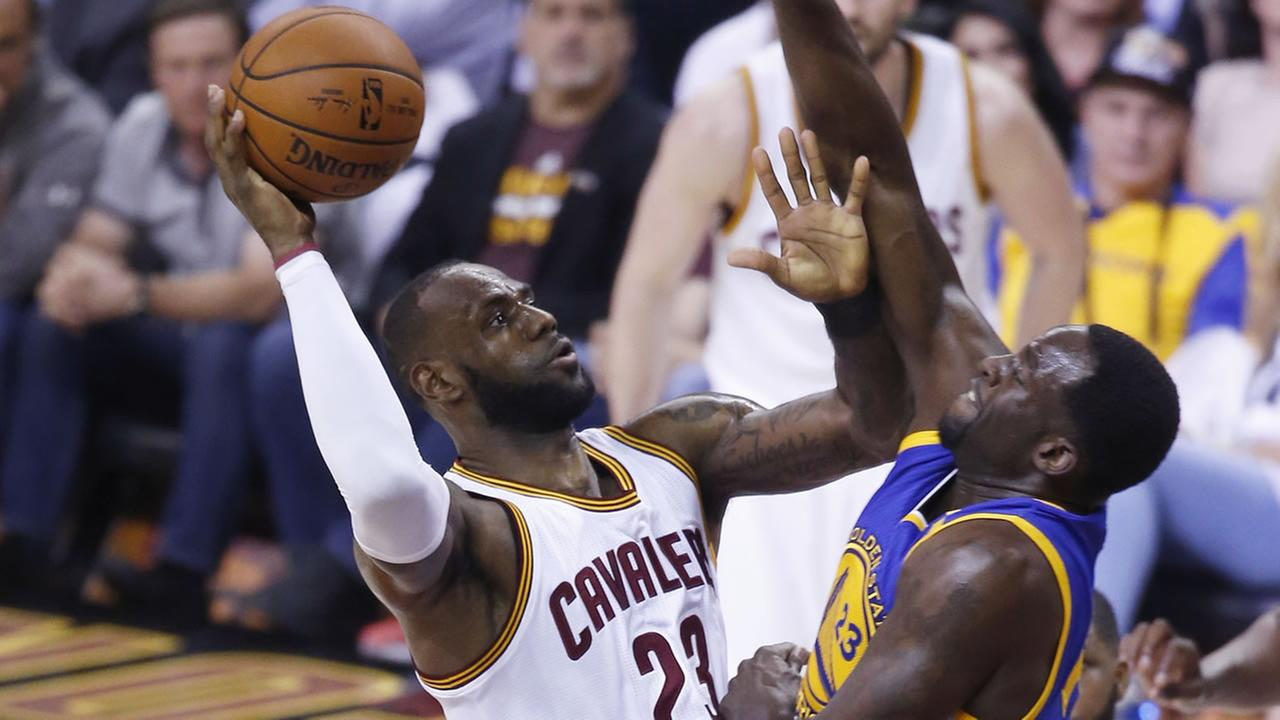 LeBron James shoots while Draymond Green guards him during Game 4 of the NBA Finals in Cleveland, Ohio on June 9, 2017.AP