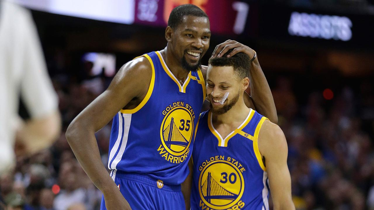 Golden State Warriors Kevin Durant (35) hugs teammate Stephen Curry (30) in Cleveland, Friday, June 9, 2017.