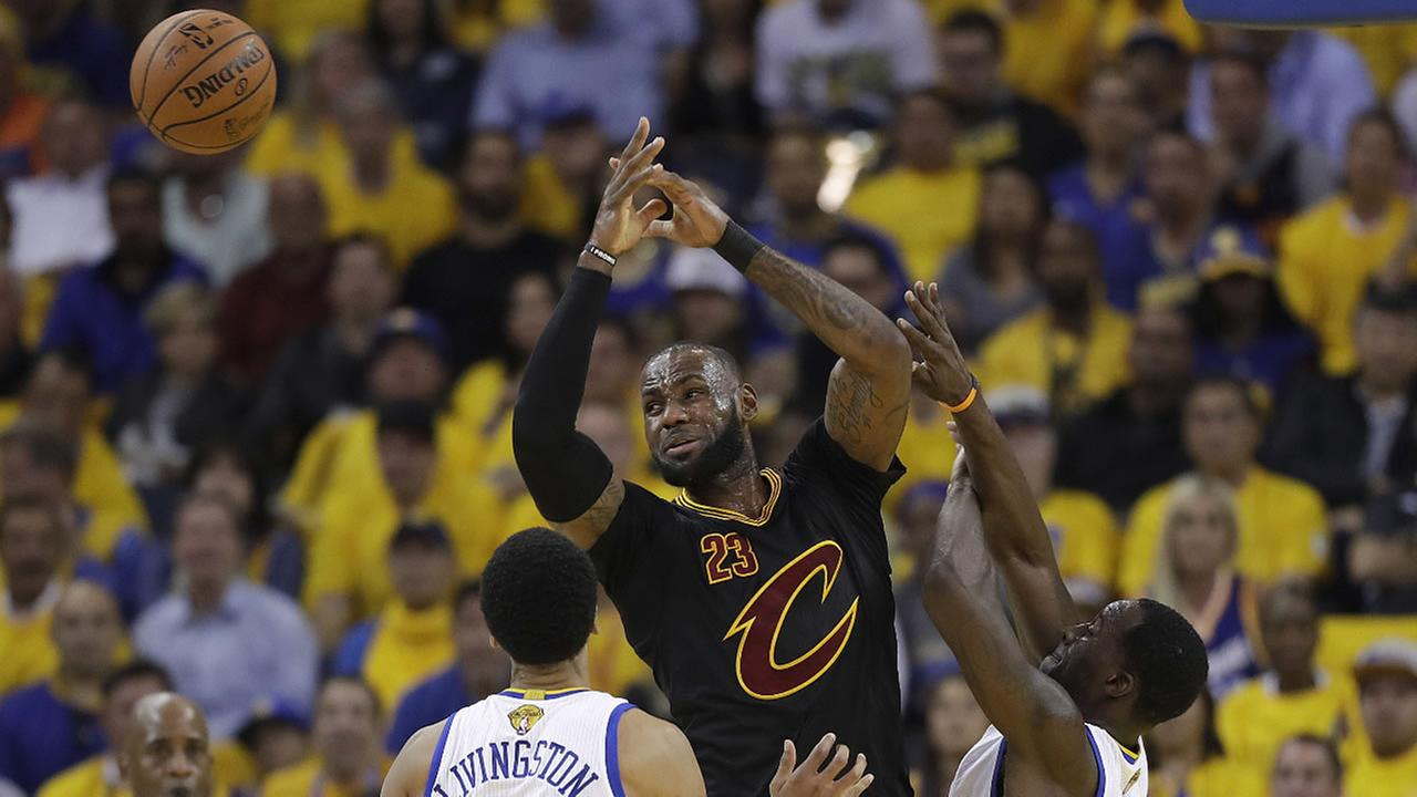 Cavaliers' James loses the ball while guarded by Warriors' Livingston during Game 5 of the NBA Finals in Oakland, Calif. Monday, June 12, 2017. (AP Photo/Marcio Jose Sanchez)