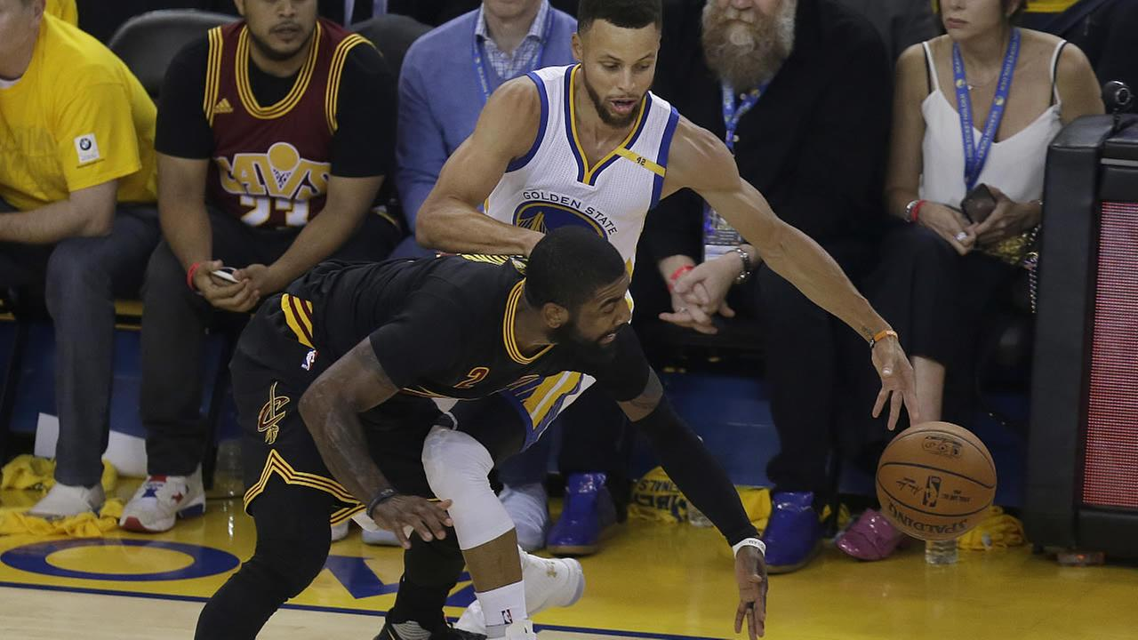 Cavaliers' Kyrie Irving reaches for the ball under Warriors' Stephen Curry during Game 5 of the NBA Finals in Oakland, Calif., Monday, June 12, 2017. (AP Photo/Ben Margot)
