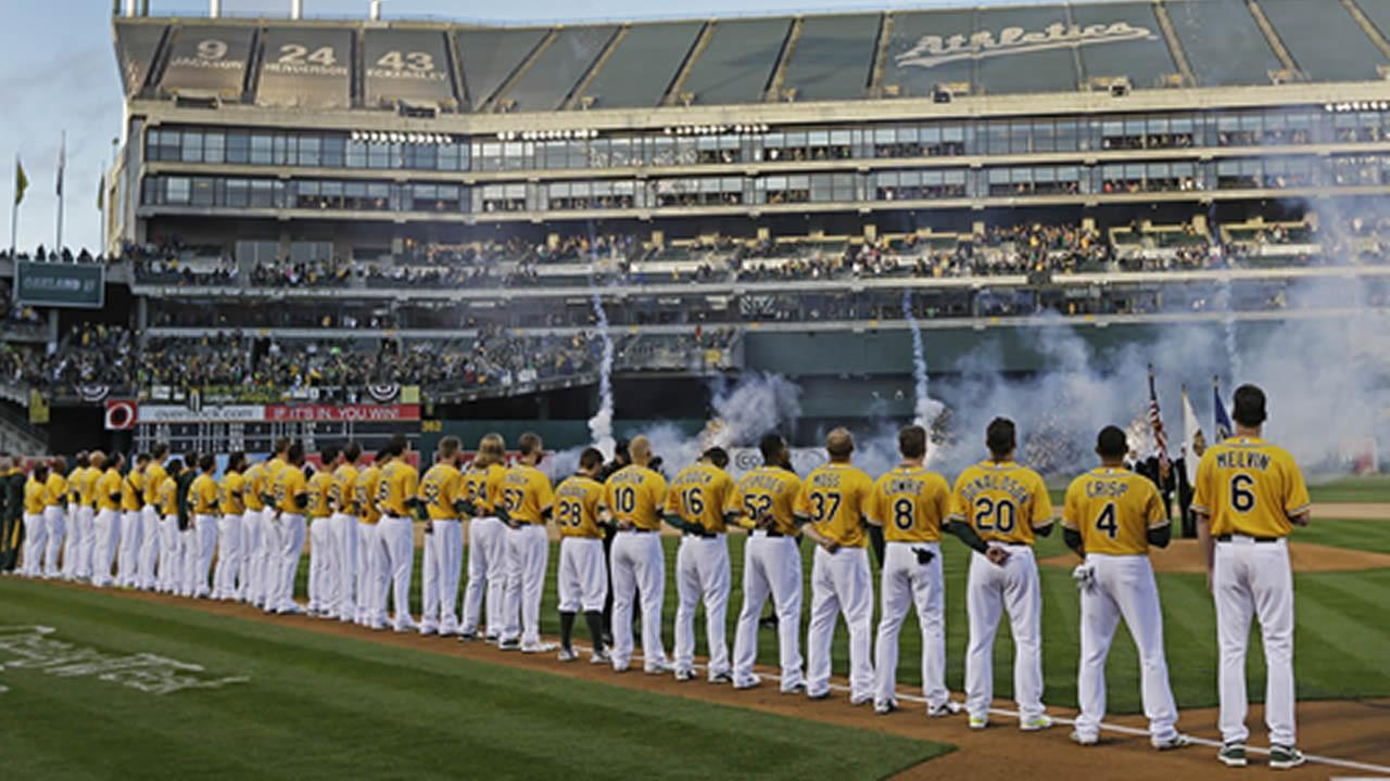 The Oakland Athletics watch a fireworks display during the national anthem prior to a baseball game against the Cleveland Indians Monday, March 31, 2014, in Oakland, Calif. (AP Photo/Ben Margot)