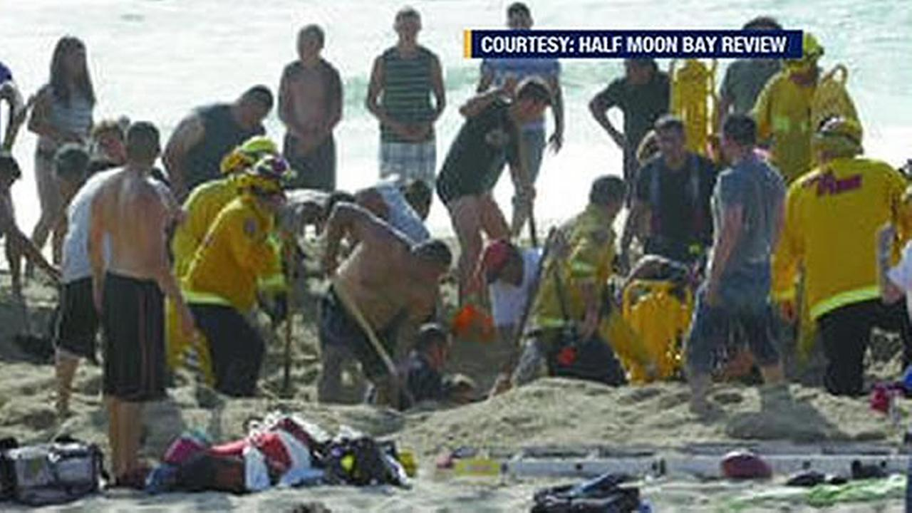 Half Moon Bay Review photo of the frantic effort to rescue a man trapped when a sand tunnel collapsed on him at a Half Moon Bay beach.