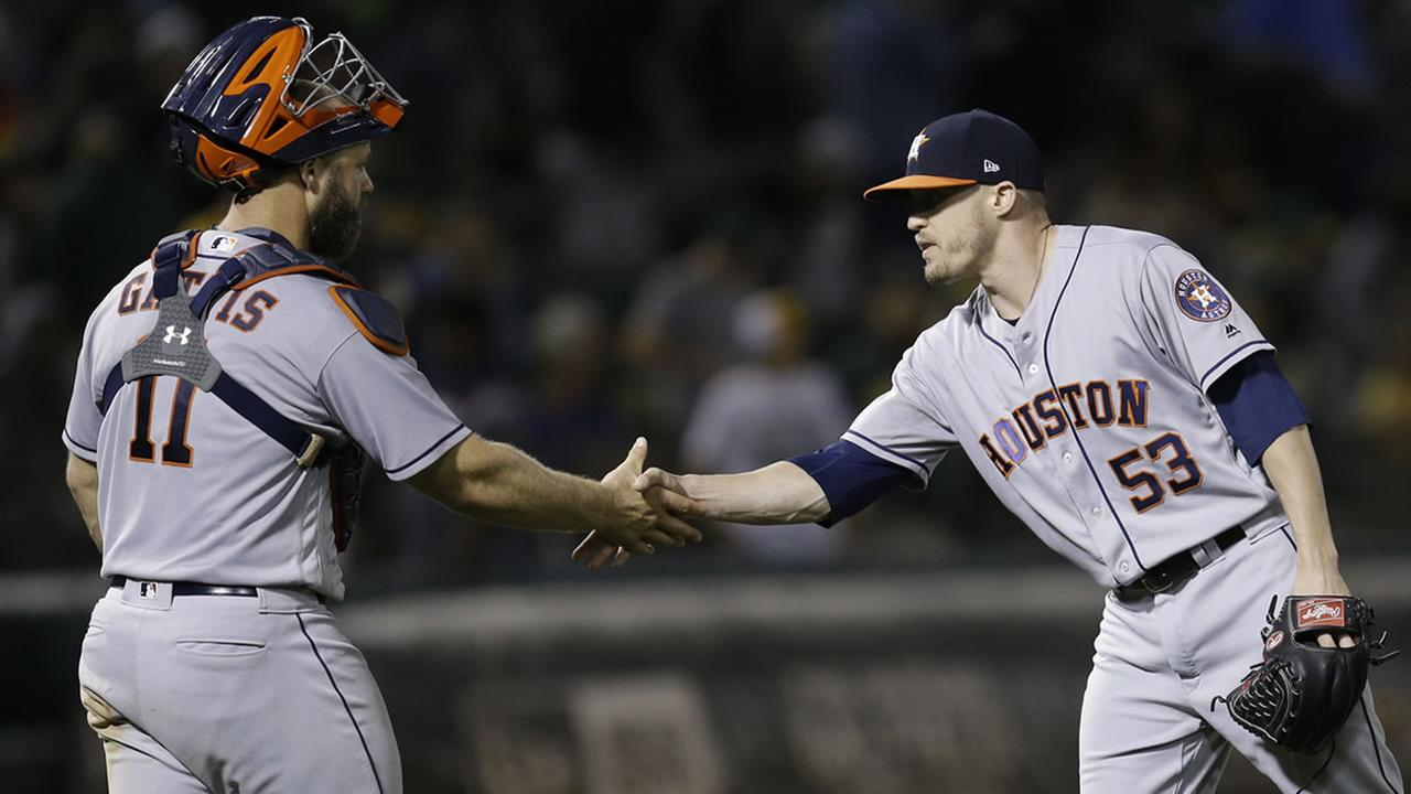 Astros pitcher Ken Giles, right, celebrates the 4-1 win over the Oakland Athletics with catcher Evan Gattis at the end of a baseball game Monday, June 19, 2017, in Oakland, Calif.