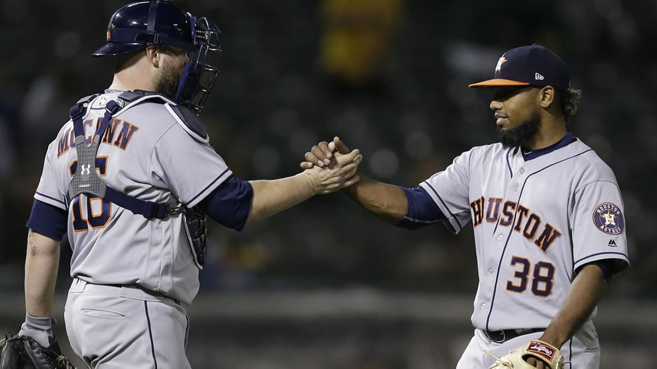 Astros pitcher Dayan Diaz, right, and Brian McCann celebrate the teams 8-4 win over the Oakland Athletics at the end of a baseball game Tuesday, June 20, 2017, in Oakland, Calif.