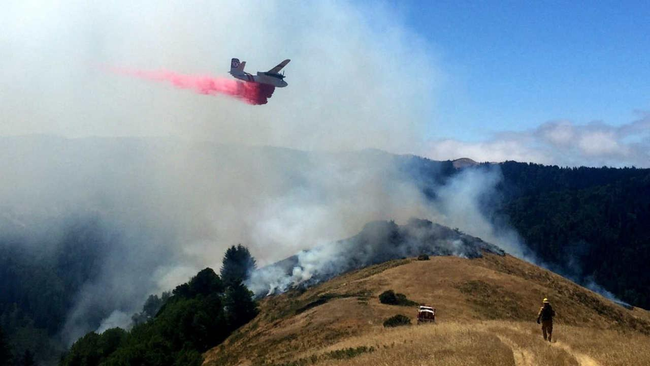 A tanker is seen dropping fire retardant on a grass fire in Marin County, Calif. on Tuesday, June 27, 2017.