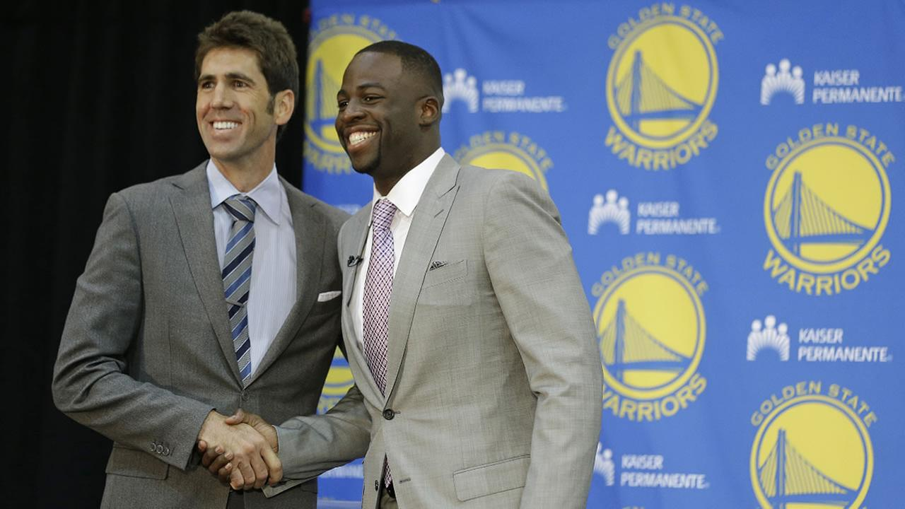 Warriors forward Draymond Green, right, shakes hands with general manager Bob Myers, left, following a news conference Thursday, July 9, 2015, in Oakland, Calif.