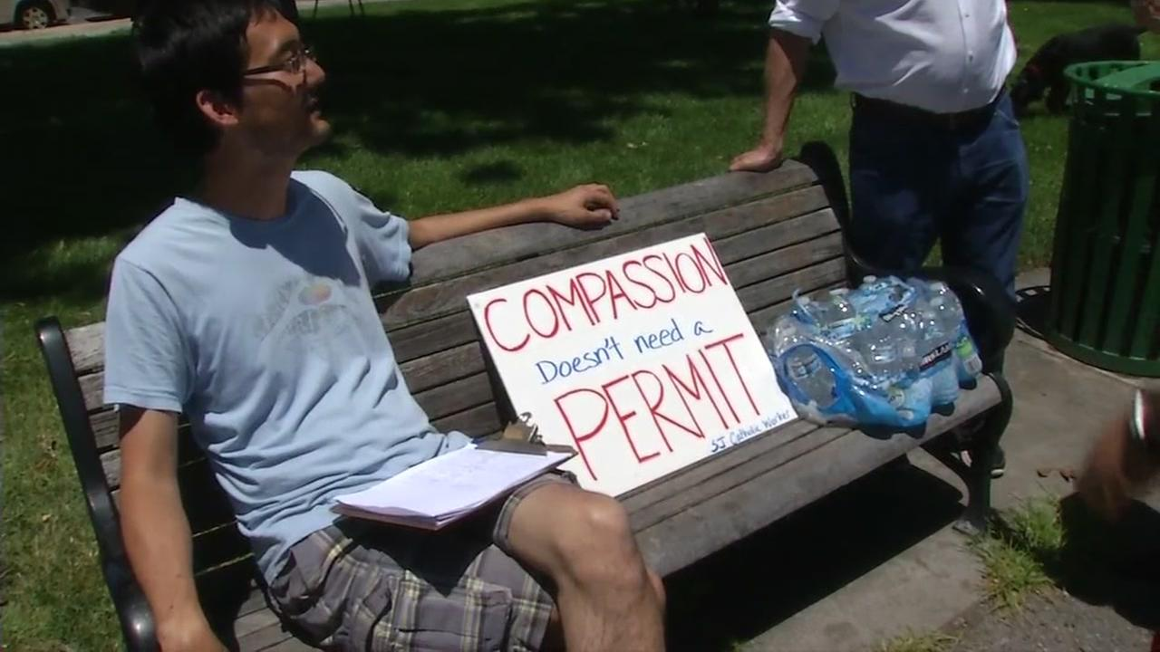 A homeless advocate sits with a sign protesting the crack down on feeding the homeless in San Jose, Calif. on Friday, June 30, 2017.
