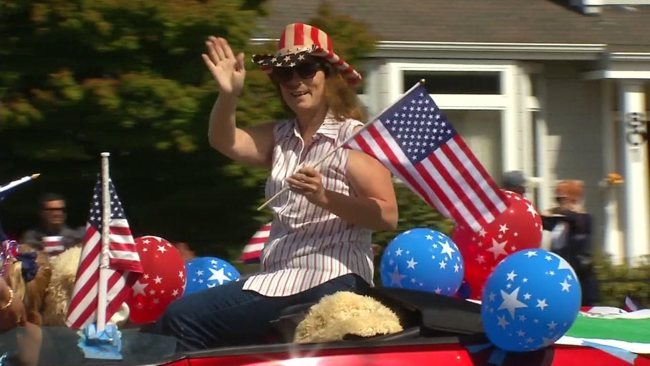 A woman waves to the crowd while riding in a 4th of July Parade in Alameda, Calif. on Tuesday, July 4, 2017.
