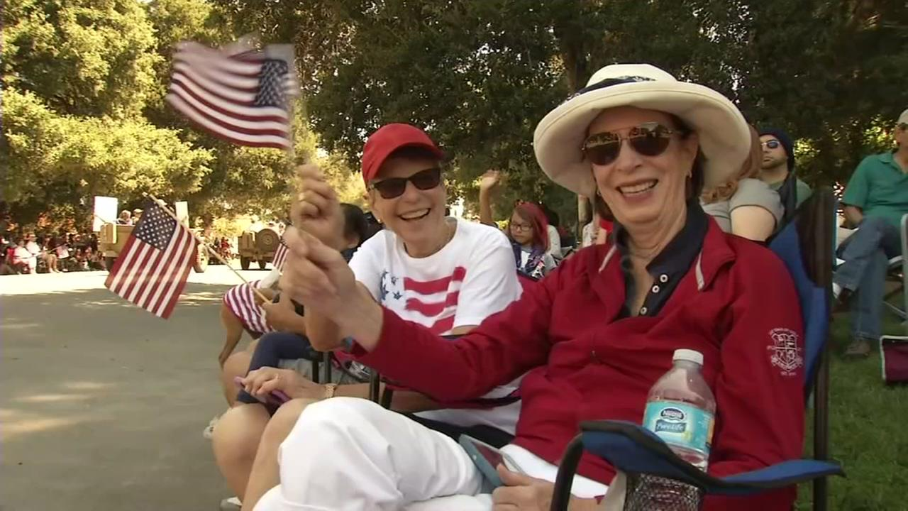 Nickie Martin and Nancy Cheso wave their flags at the Rose White and Blue Parade in San Jose, Calif. on Tuesday, July 4, 2017.