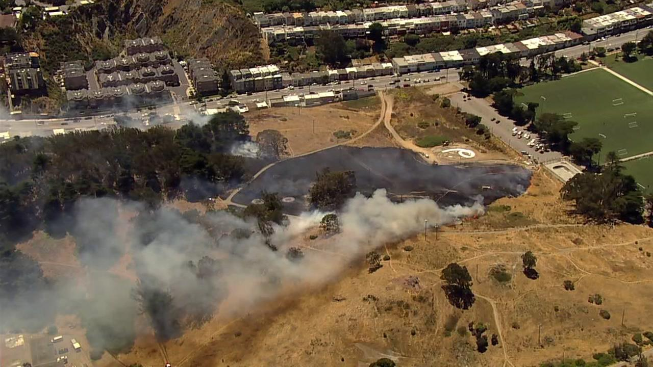 A grass fire burns near the Crocker Amazon Playground in San Francisco on Friday, July 7, 2017.KGO-TV