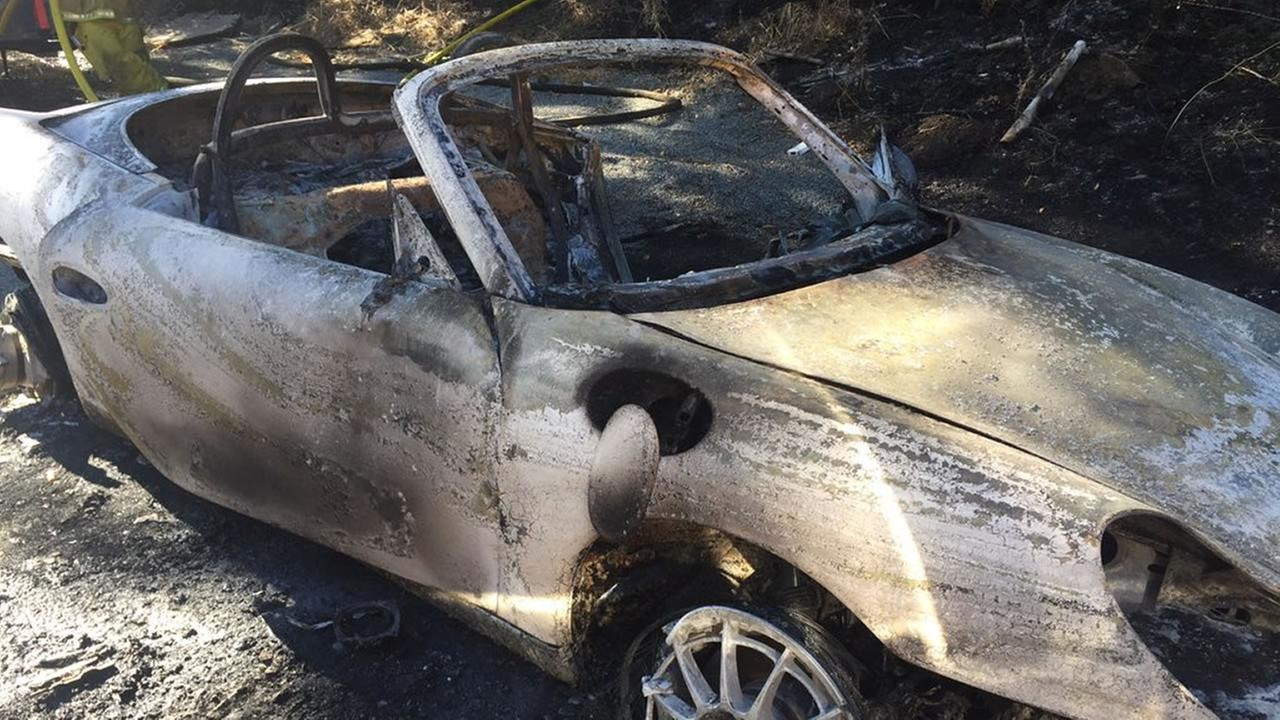 A mans car appears in San Jose, Calif. after catching fire and sparking a nearby brush fire on Monday, July 10, 2017.