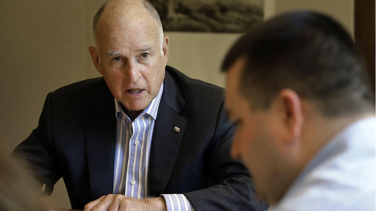 FILE - In this July 7, 2017, photo, California Gov. Jerry Brown discusses a bill with Chris Ferguson, right, a principal program budget analyst in Sacramento, Calif. (AP Photo)