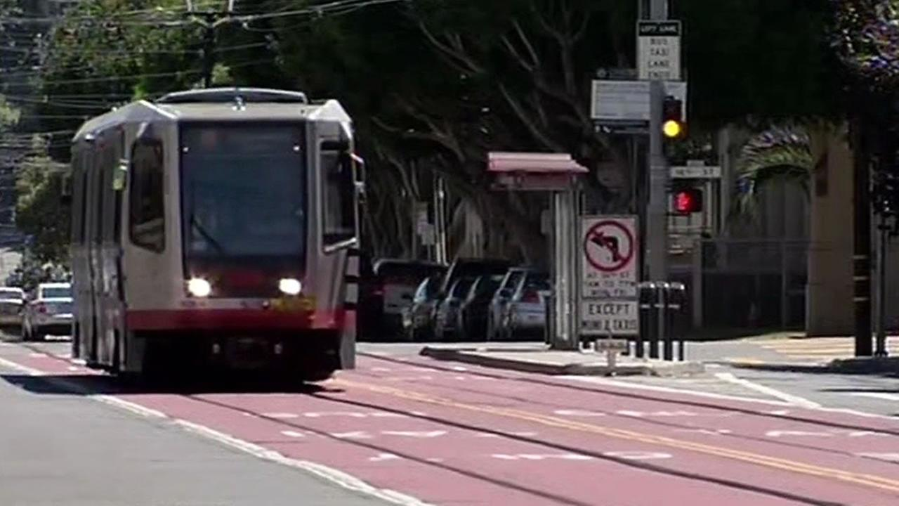 Muni train drives along red marked transit-only lanes in San Francisco