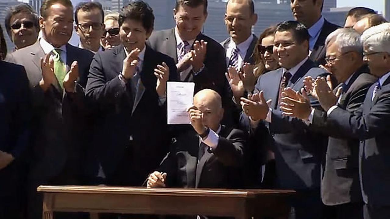 Governor Jerry Brown is seen signing a landmark climate change bill on Treasure Island on Tuesday, July 25,2017.