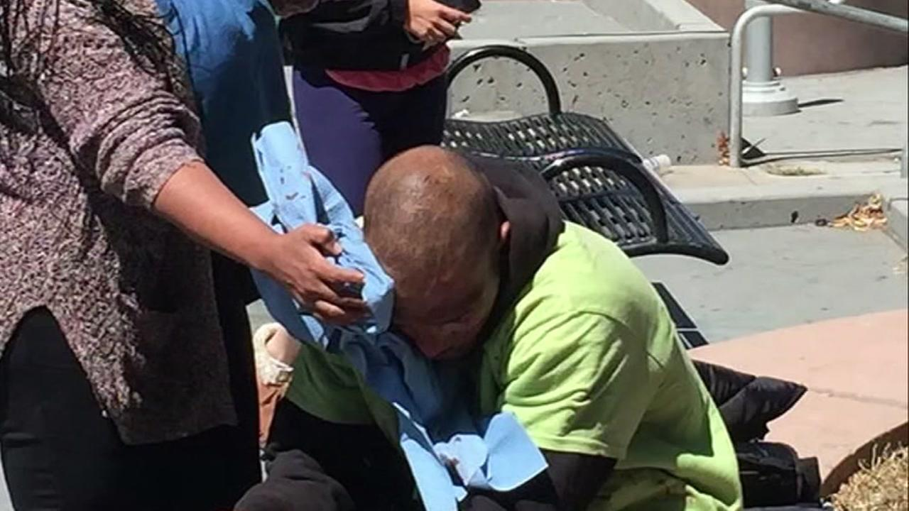 This image shows two women helping a man who was allegedly attacked near the BART station in Richmond, Calif. on Thursday, July 20, 2017.