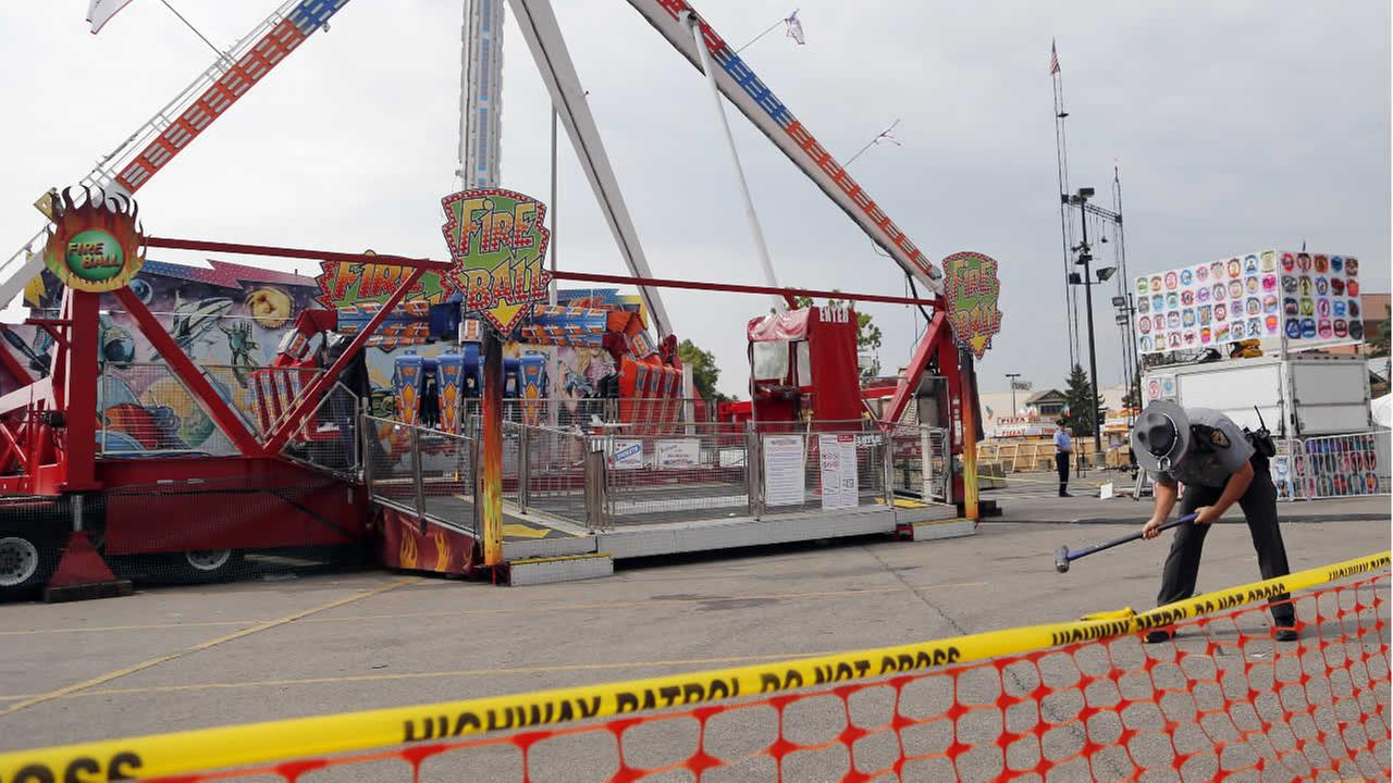 An Ohio State Highway Patrol trooper removes a ground spike from in front of the fire ball ride at the Ohio State Fair Thursday, July 27, 2017, in Columbus, Ohio. (AP Photo)