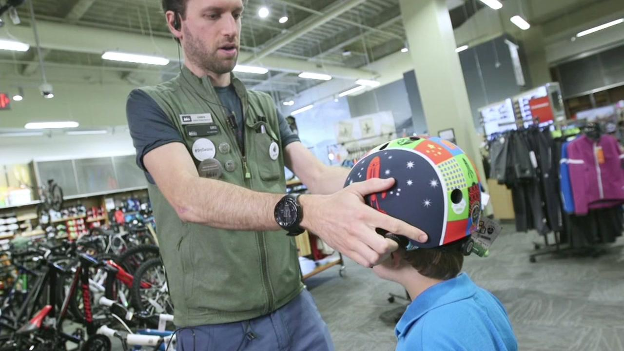This is an undated image of a man helping a child adjust a bike helmet.