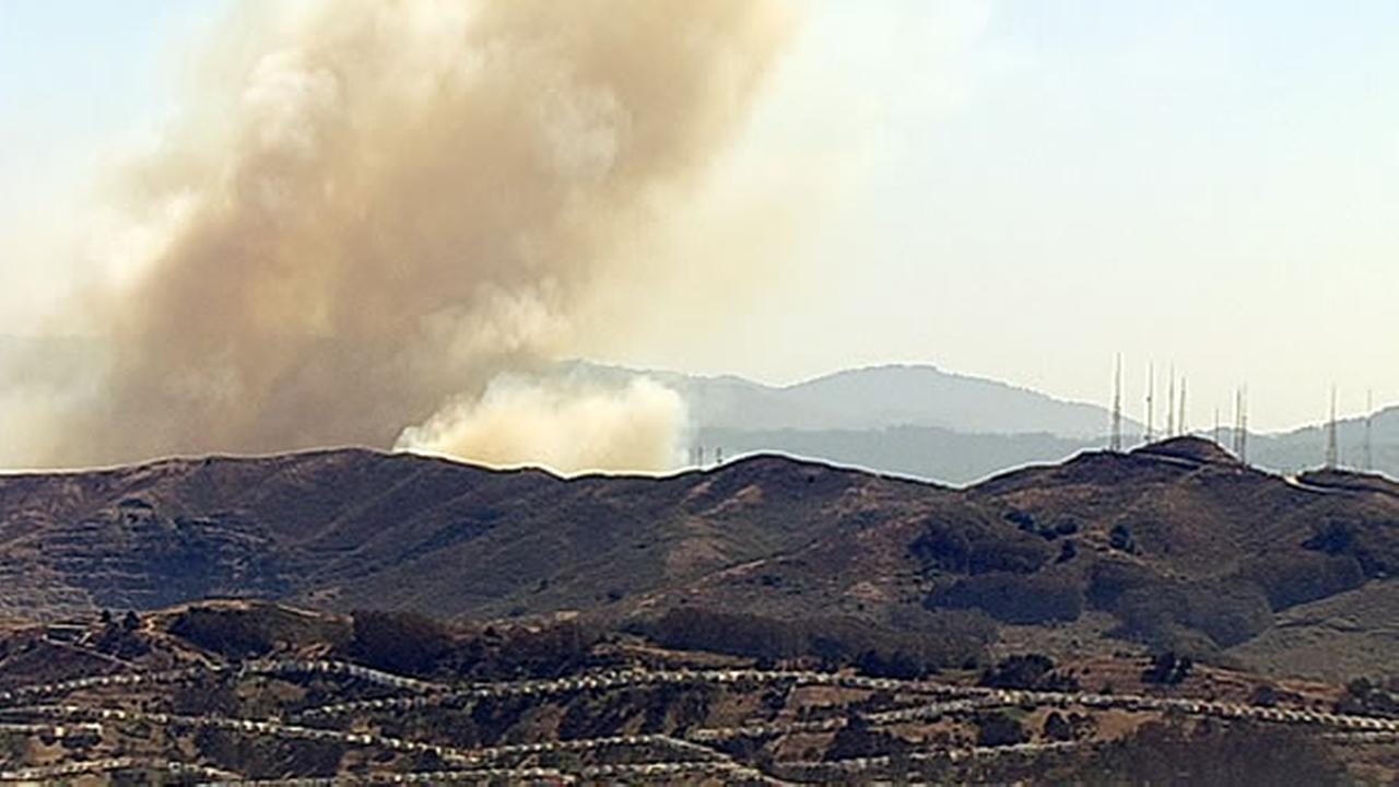 A four-alarm fire burning on San Bruno Mountain sent a large plume of smoke in the air that was visible from several miles away.