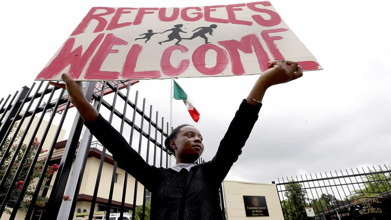 Zelda holds up a sign as she joins demonstrators outside the Mexican Consulate Friday, July 18, 2014, in Houston. (AP Photo/David J. Phillip)