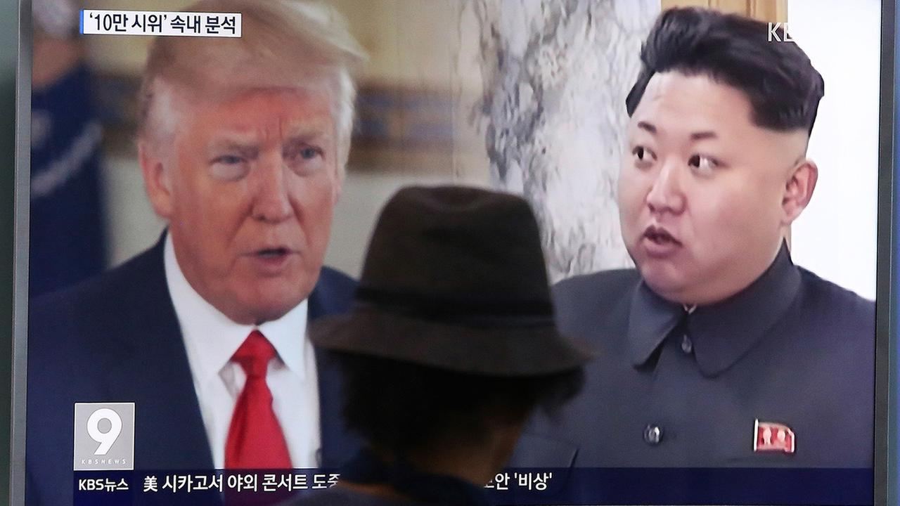 A man watches a TV showing U.S. President Donald Trump, left, and North Korean leader Kim Jong Un in Seoul, South Korea, Thursday, Aug. 10, 2017.