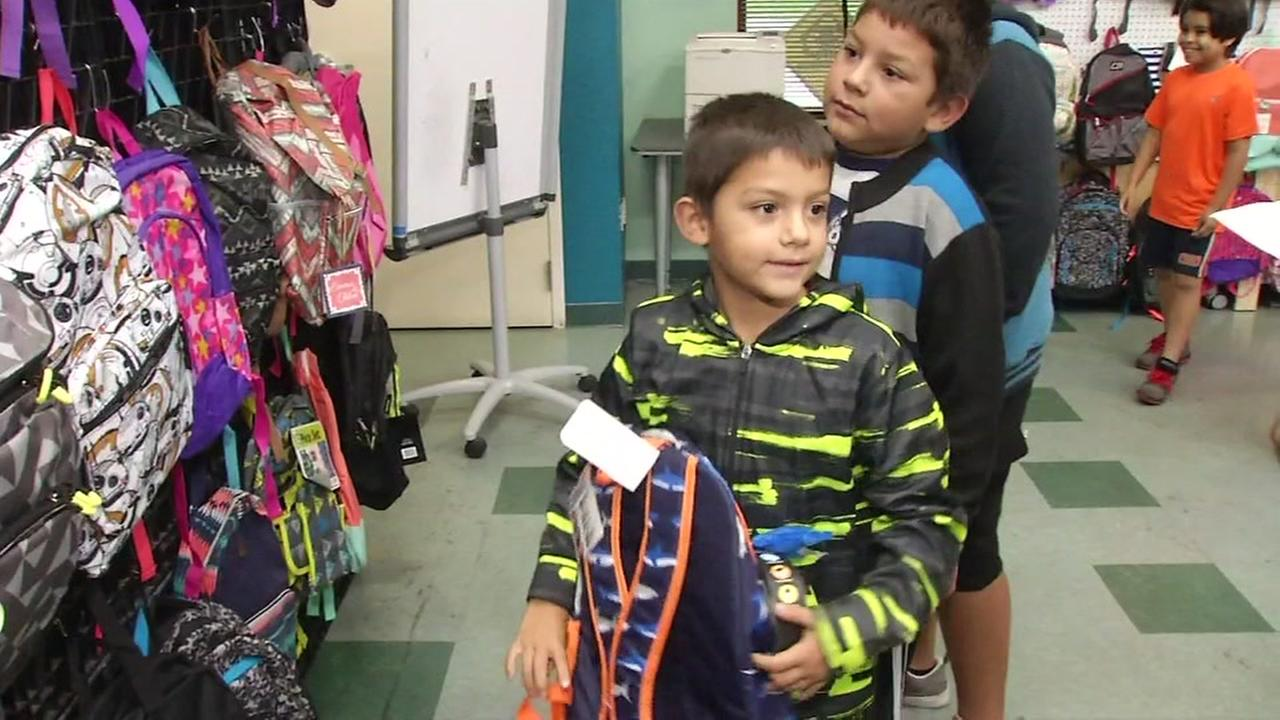 Boy gets backpack at Scared Heart Community Service in San Jose, California, Friday, August 11, 2017.