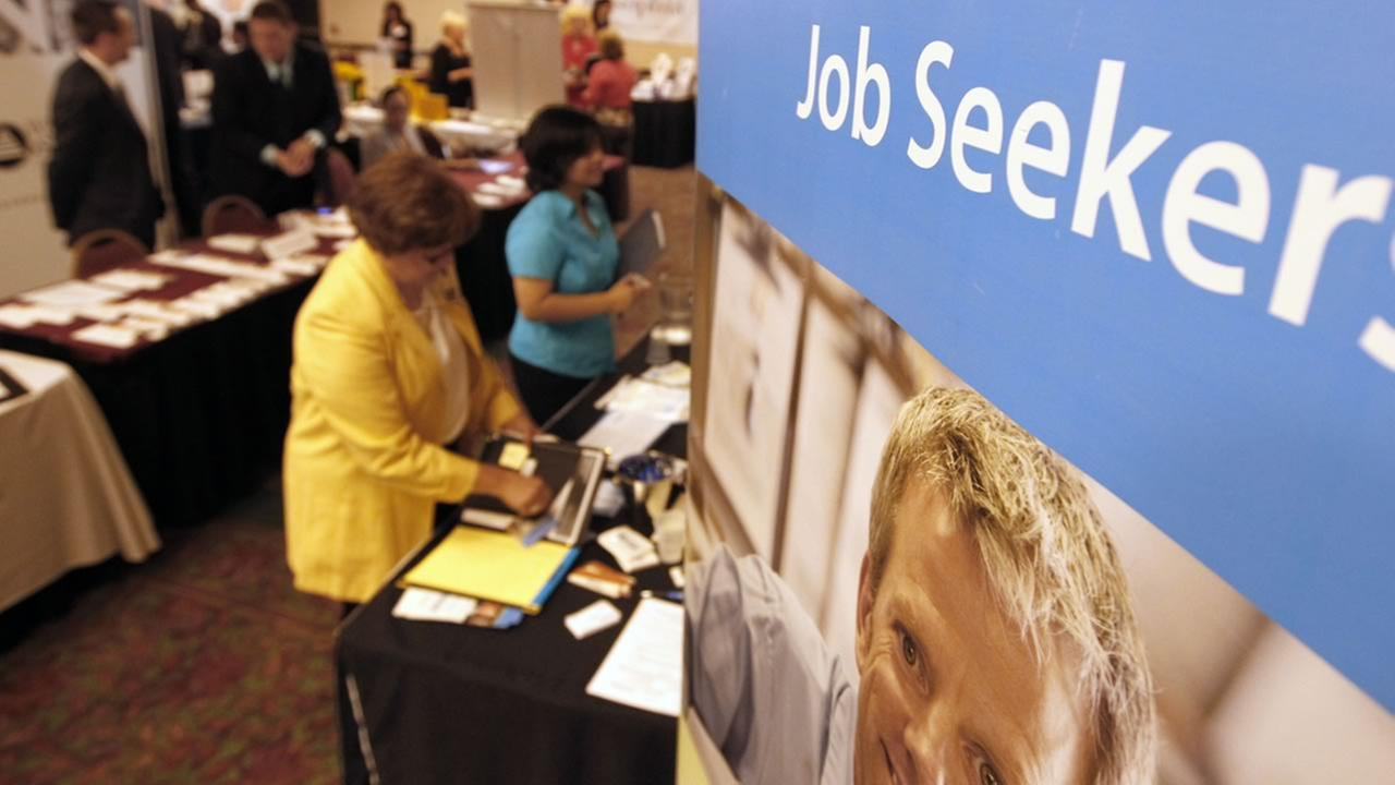 In this Tuesday, July 10, 2012 photo, people walk by the recruiters at a jobs fair in the Pittsburgh suburb of Green Tree, Pa. (AP Photo/Keith Srakocic)