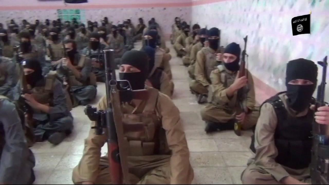 This undated image shows ISIS fighters armed with guns gathered in a room.