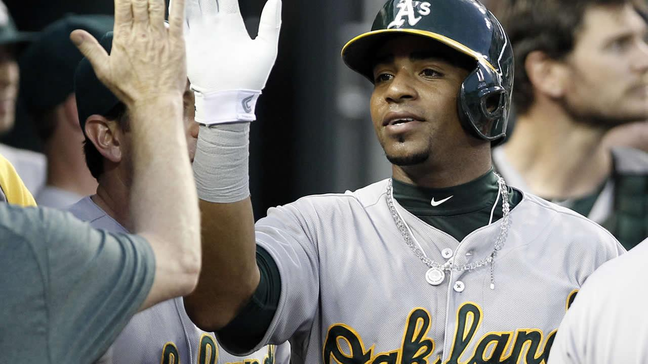 Oakland Athletics Yoenis Cespedes gets a high-five after scoring on a single by Jed Lowrie during a baseball game against the Detroit Tigers June 30, 2014, in Detroit. (AP Photo/Duane Burleson)