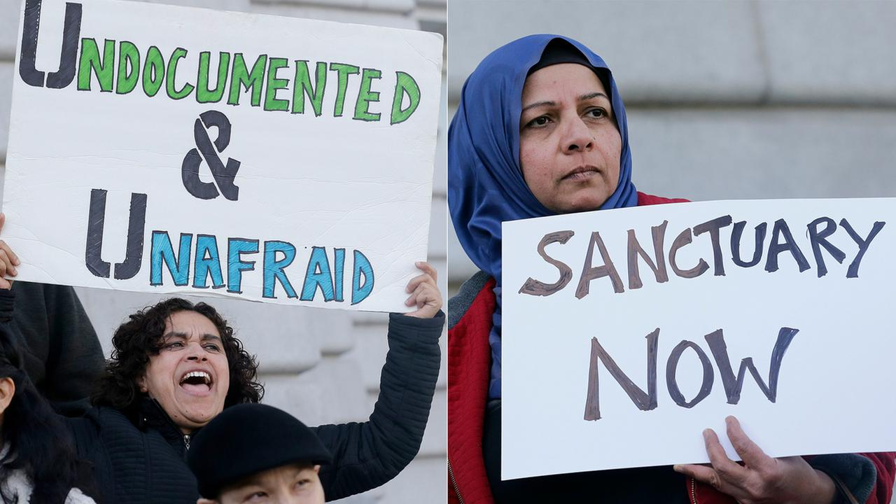 Lordes Reboyoso, left, and Moina Shaiq hold signs at a rally outside of City Hall in San Francisco, Wednesday, Jan. 25, 2017. (AP Photo/Jeff Chiu)