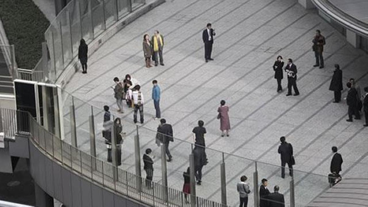 Office workers in Tokyos Shiodome district near Tokyo Bay stay on the pedestrian deck Friday, March 11, 2011, shortly after a 7.9-magnitude earthquake has struck off Japans northeastern coast. (AP Photo/Koji Sasahara)AP Photo/Koji Sasahara