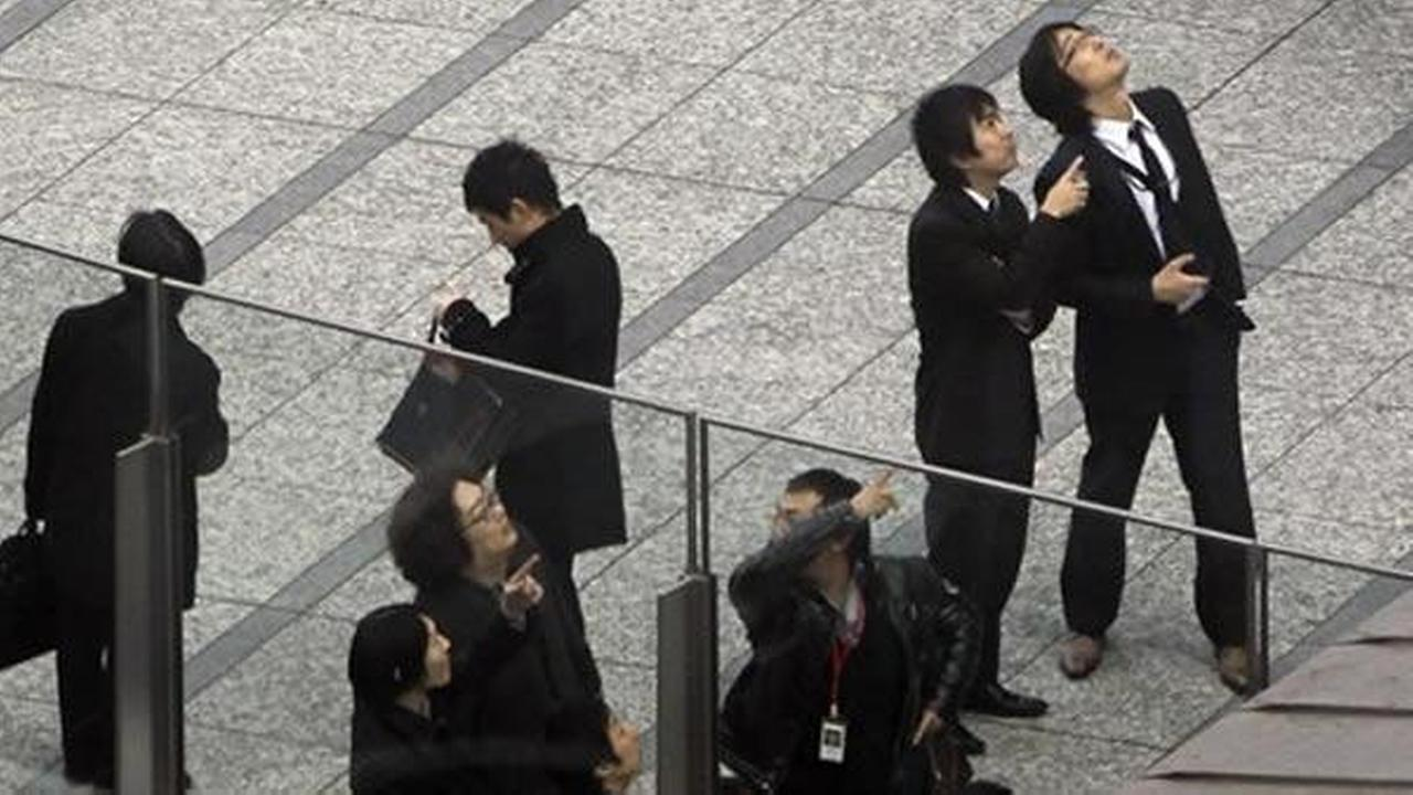 Office workers in Tokyos Shiodome district near Tokyo Bay stay on the pedestrian deck, observing surrounding high-rise office and hotel buildings swaying Friday, March 11, 2011, shortly after a 7.9-magnitude earthquake has struck off Japans northeastern coast. (AP Photo/Koji Sasahara)AP Photo/Koji Sasahara