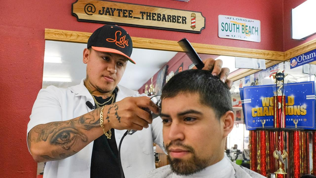 JayTee the Barber cuts a clients hair in Santa Rosa, Calif. on Tuesday, Aug. 15, 2017.