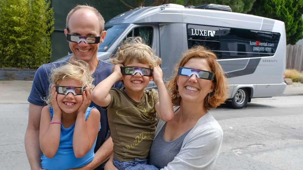 The Wendl family tries on the eclipse glasses before hopping in the van in front of their San Francisco home on Friday, August 18, 2017.
