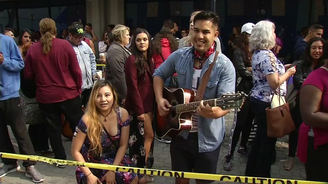 An American Idol contestant plays guitar while another sings in Oakland, Calif. on Aug. 20, 2017.KGO-TV