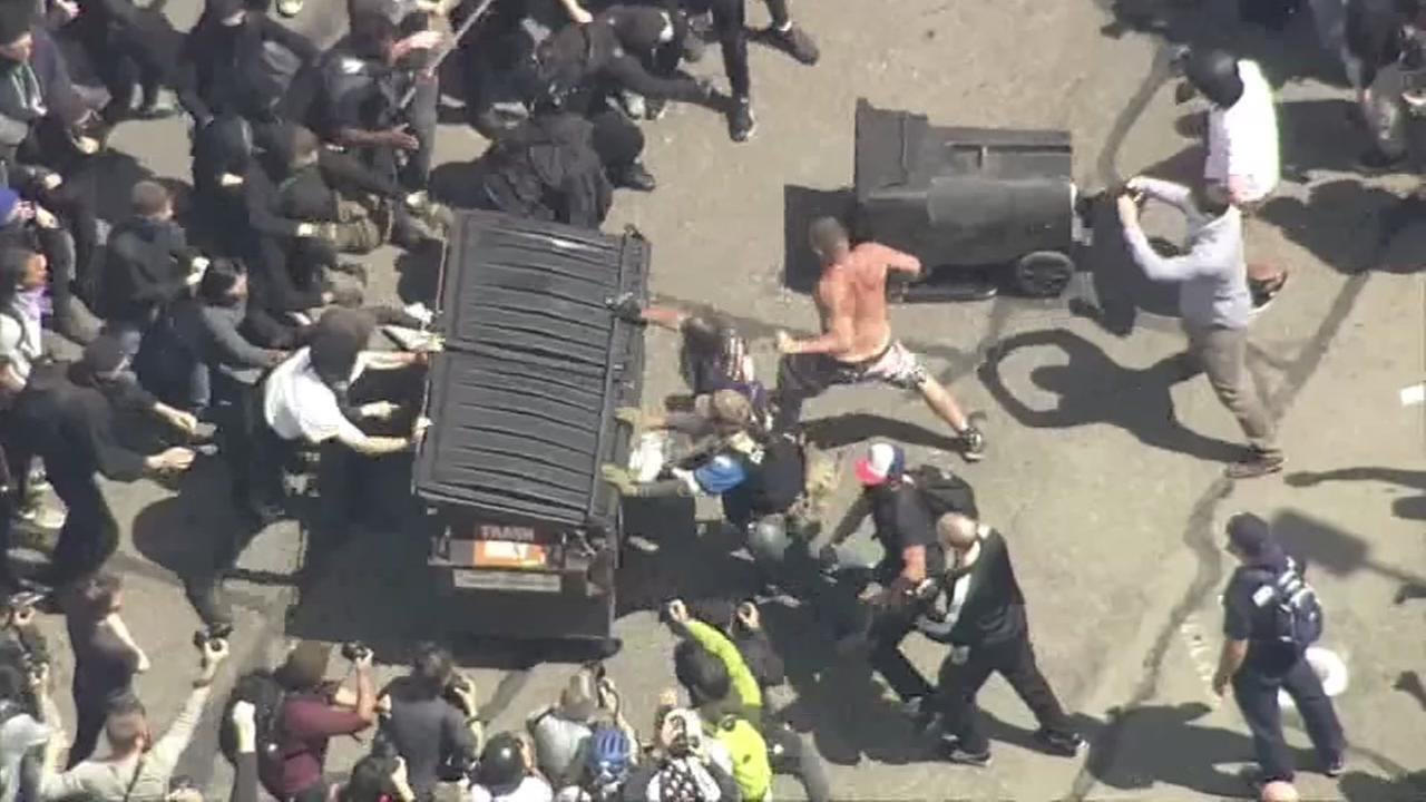 Protesters tip over a car in this undated image.