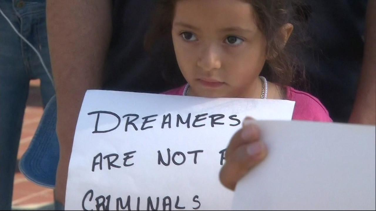 A little girl holds a sign that reads, Dreamers are not criminals at a protest in Berkeley, Calif. on Monday, Sept. 4, 2017.