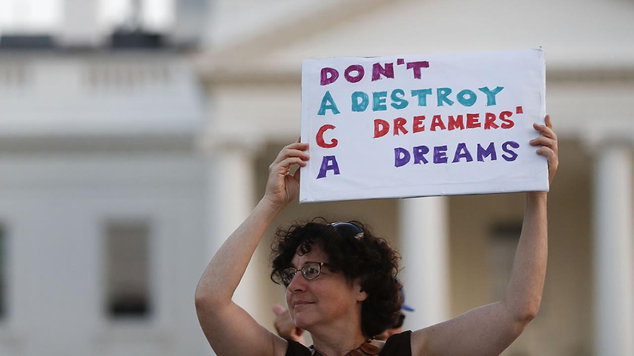 Julia Paley, of Arlington, Va., with the DMV Sanctuary Congregation Network, holds up a sign outside the White House, in Washington, Monday, Sept. 4, 2017.