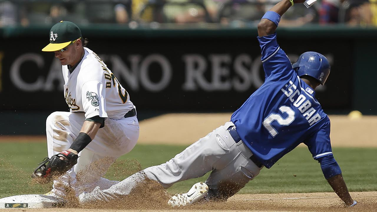Royals Alcides Escobar, right, advances to third base past the tag of Oakland As Josh Donaldson at a baseball game Sunday, Aug. 3, 2014,  in Oakland, Calif. (AP Photo/Ben Margot)