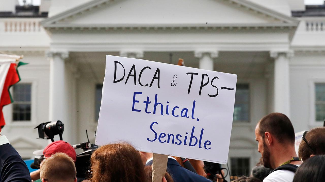 A person holds up a sign in support of the Deferred Action for Childhood Arrivals, known as DACA, during a rally outside of the White House, in Washington, Tuesday, Sept. 5, 2017.