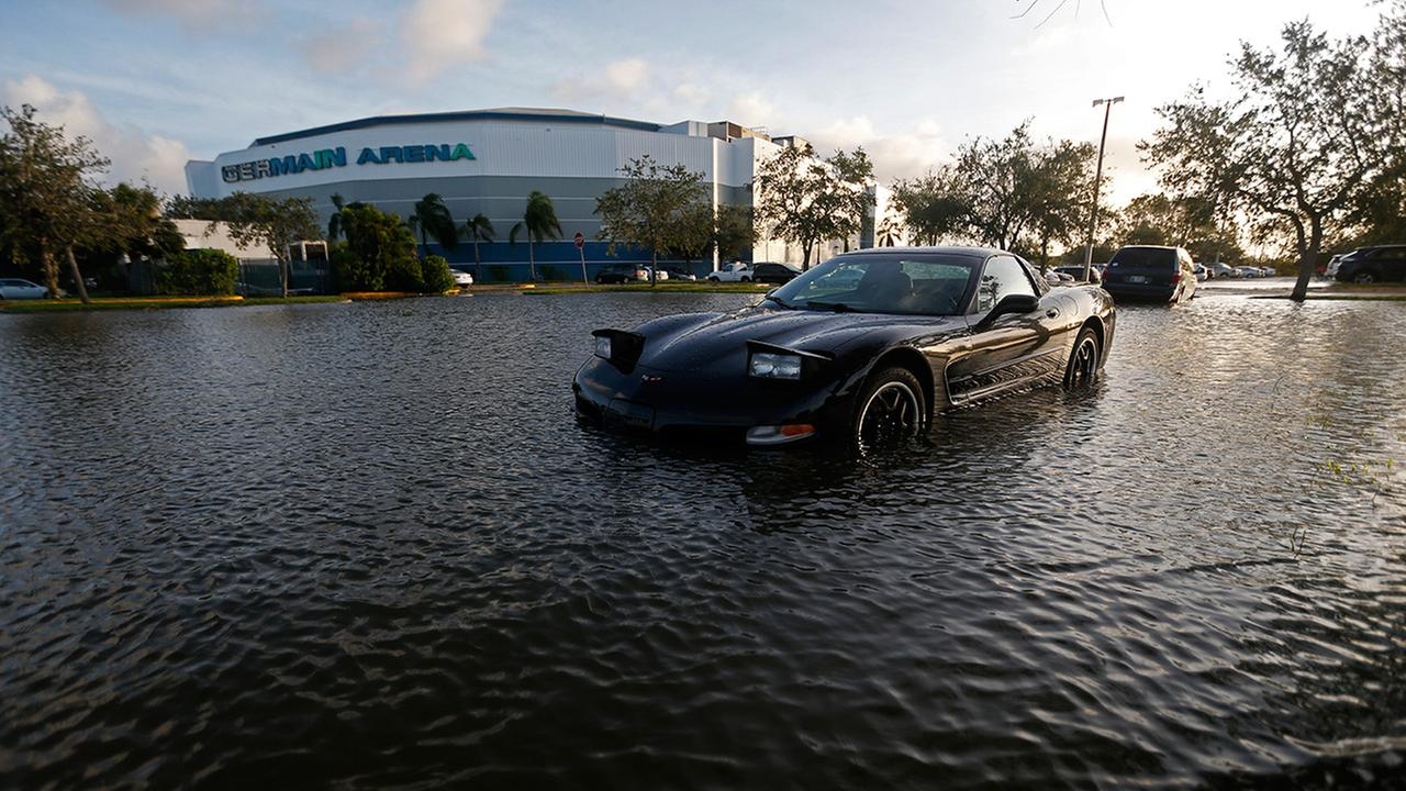A car sits in a flooded parking lot outside the Germain Arena, which was used as an evacuation shelter for Hurricane Irma, which passed through yesterday, in Estero, Fla., Monday, Sept. 11, 2017. (AP Photo/Gerald Herbert)