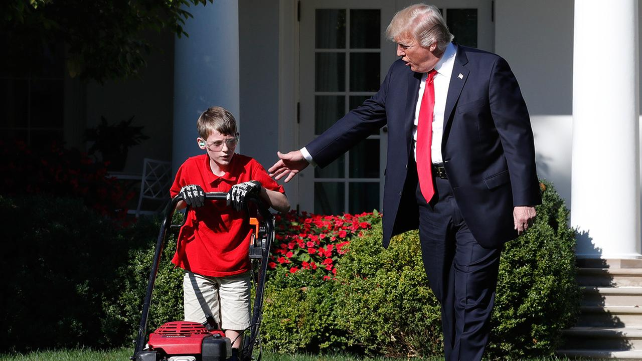 President Donald Trump walks with Frank Giaccio, 11, of Falls Church, Va., left, as he mows the lawn of the Rose Garden, Friday, Sept. 15, 2017, at the White House in Washington.