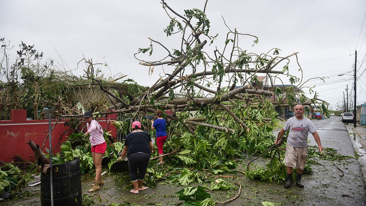 A family helps clean the road after Hurricane Maria hit the eastern region of the island, in Humacao, Puerto Rico, Wednesday, September 20, 2017.