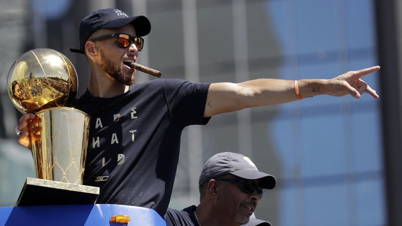 FILE - In this June 15, 2017, Warriors Stephen Curry gestures while holding the Larry OBrien trophy during a parade in Oakland, Calif.  (AP Photo/Marcio Jose Sanchez, File)