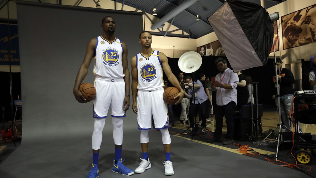 Warriors Kevin Durant, left, and Stephen Curry pose for photos during NBA basketball media day Monday, Sept. 26, 2016, in Oakland, Calif.