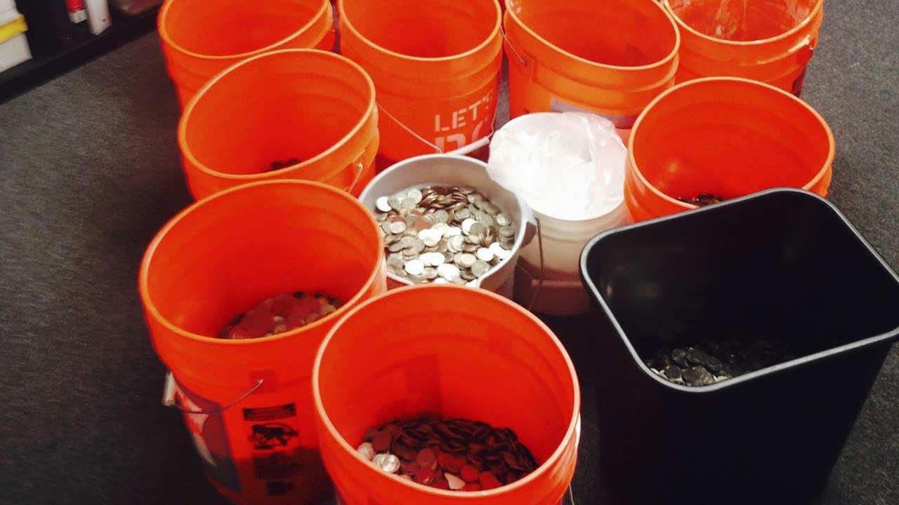 This image provided by Andres Carrasco shows him in his office in Los Angeles, July 31, 2014 with buckets of change he won as a partial settlement in a 2012 lawsuit. (AP Photo)