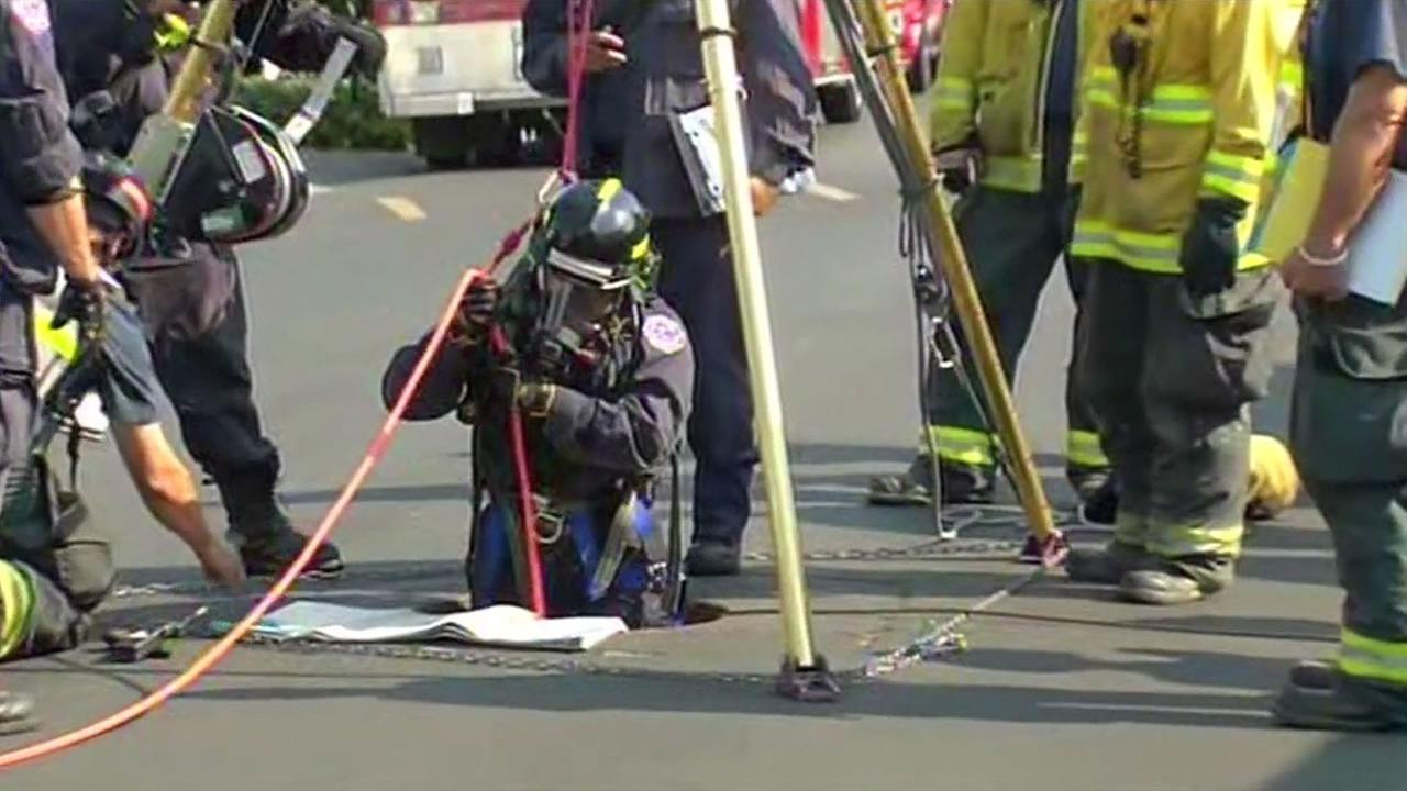 A firefighters climbs into a manhole at a mobile home park on Senter Road in San Jose.