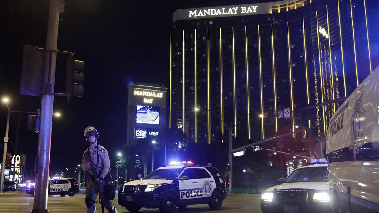 Police officers stand along the Las Vegas Strip the Mandalay Bay resort and casino during a shooting near the casino, Sunday, Oct. 1, 2017, in Las Vegas. (AP Photo/John Locher)