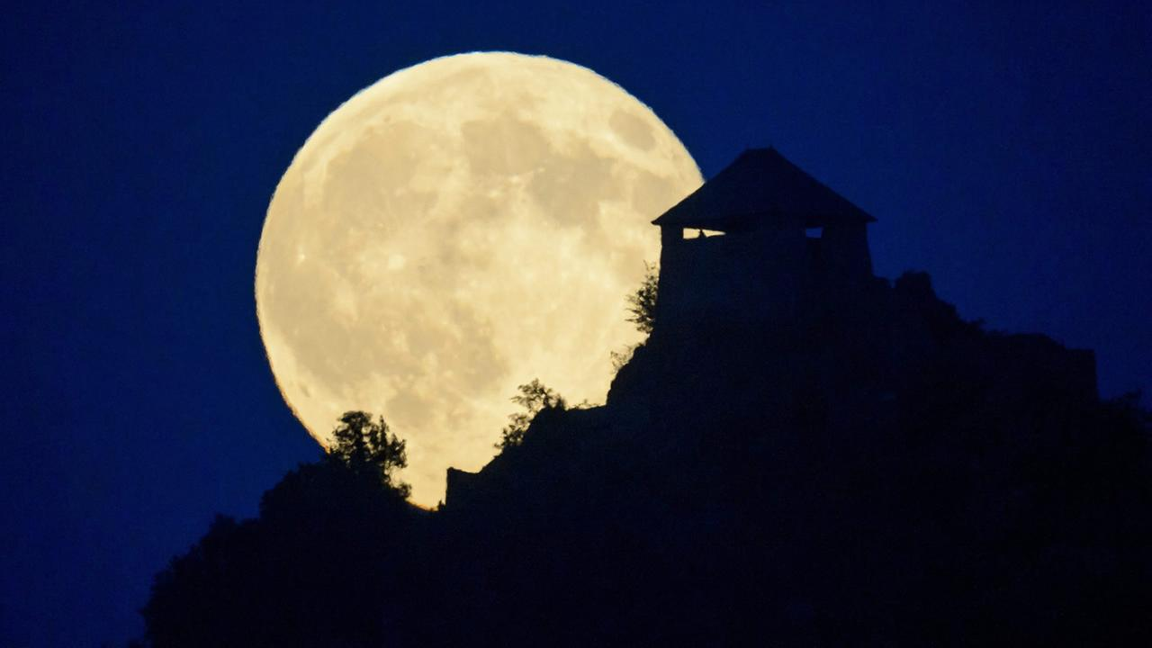 The full moon rises above the castle of Somoskoujfalu, 123 kms northeast of Budapest, Hungary, late Saturday, July 12,2014. (AP Photo/MTI,Peter Komka)